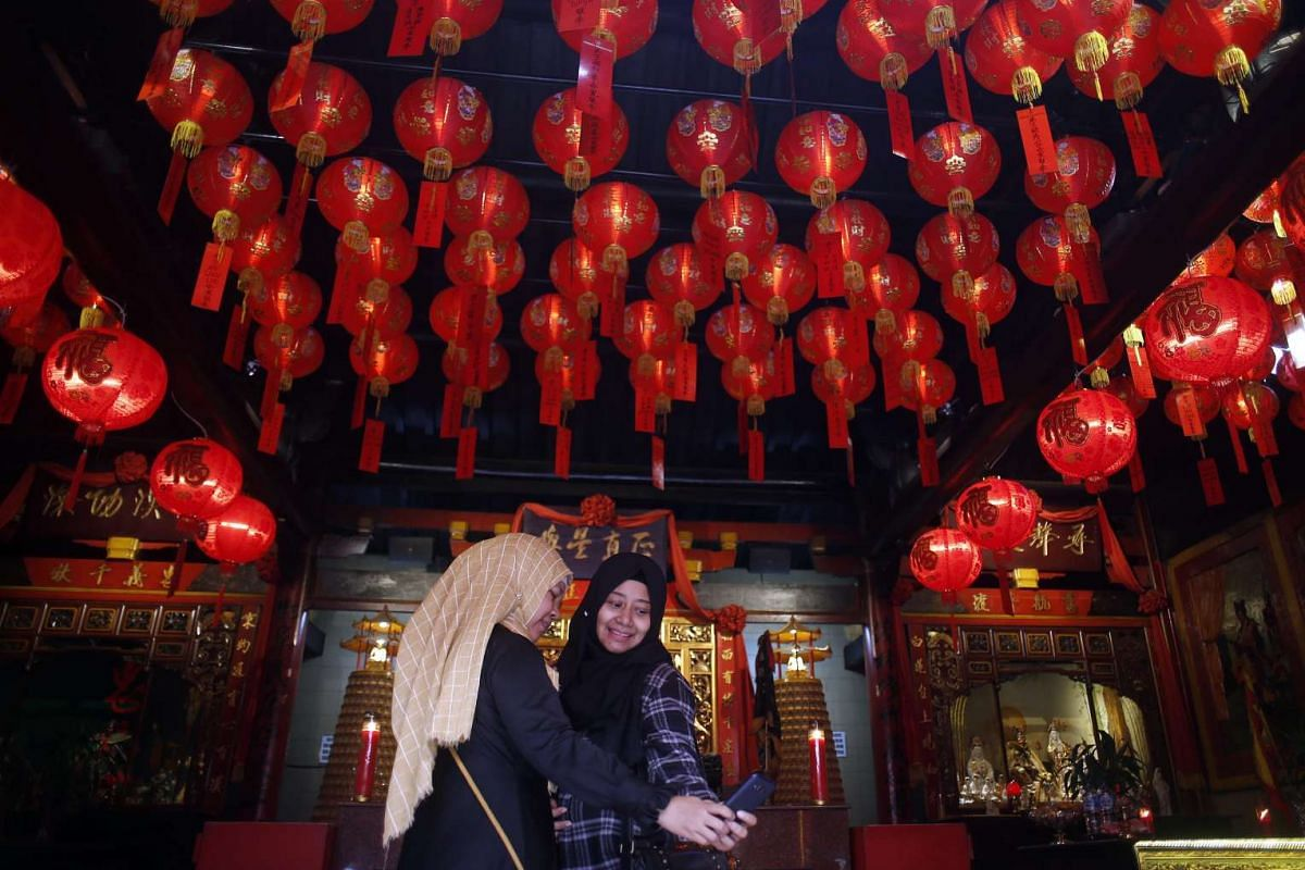 Two Indonesian Muslim women take selfies during preparations for the Chinese Lunar New Year at a temple in Bogor, Indonesia, on Feb 3, 2016.