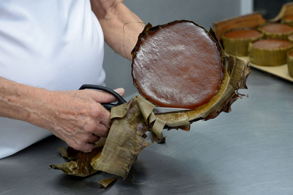 After the niangao has been steamed for eight hours and cooled, the portion of the banana leaves above the tin is trimmed off.