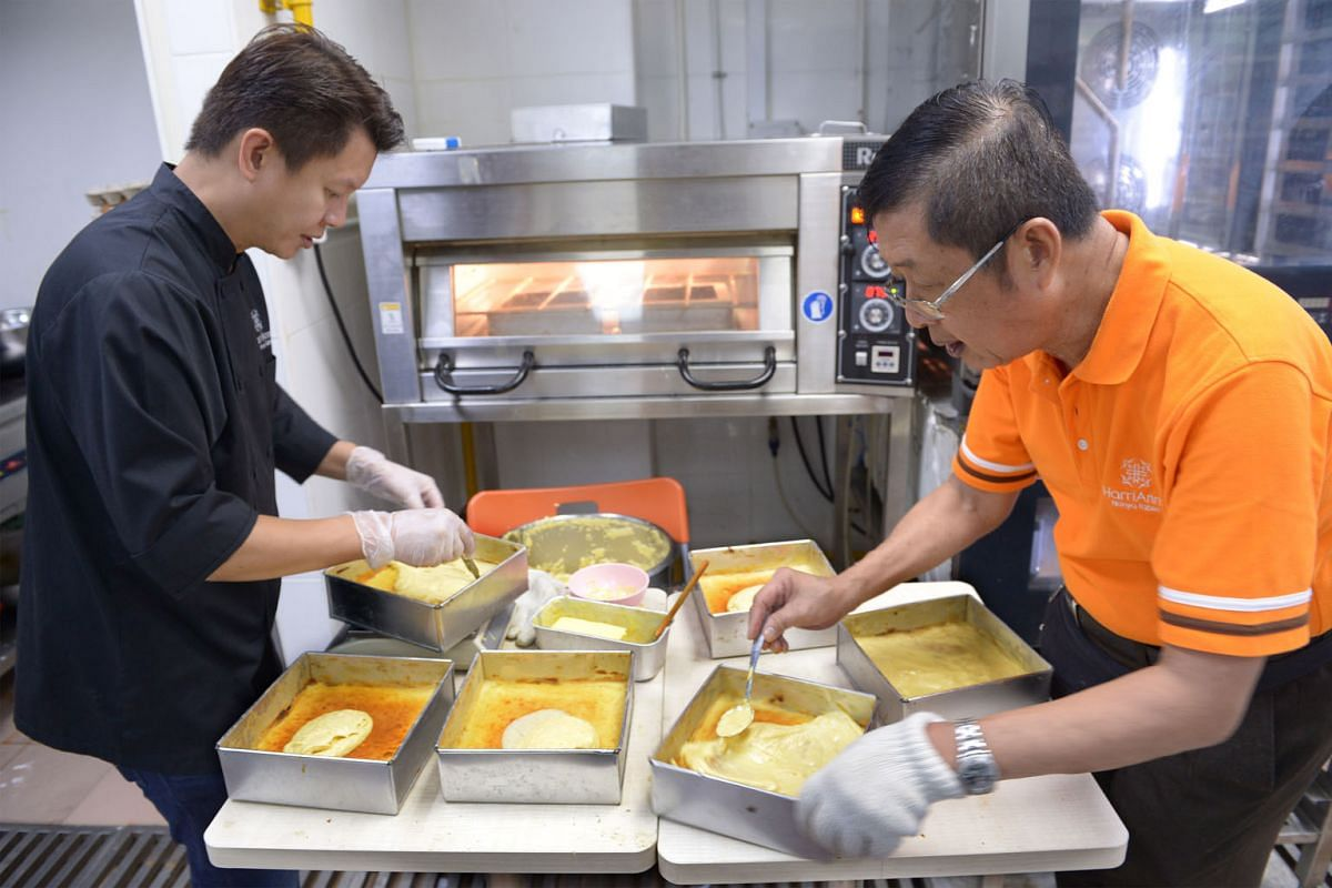 Mr Alan Tan (in black) and his father, Harry, adding a new layer of batter onto kueh lapis legit. The labour-intensive process has no shortcuts.