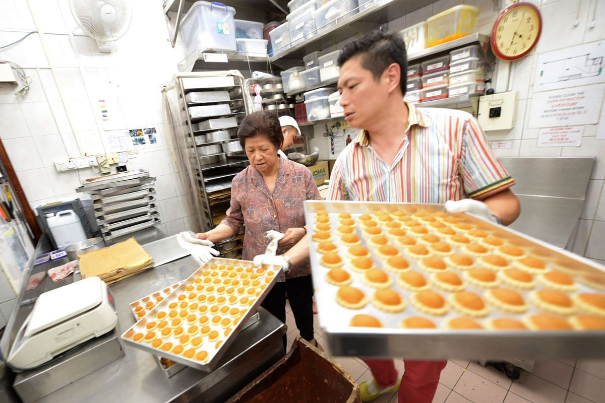 Madam Lee, one of the founders of Pine Garden's Cake, and Mr Wei, her nephew and managing director, putting pineapple tarts into the oven. The shop's pineapple tarts are ranked among the best here.