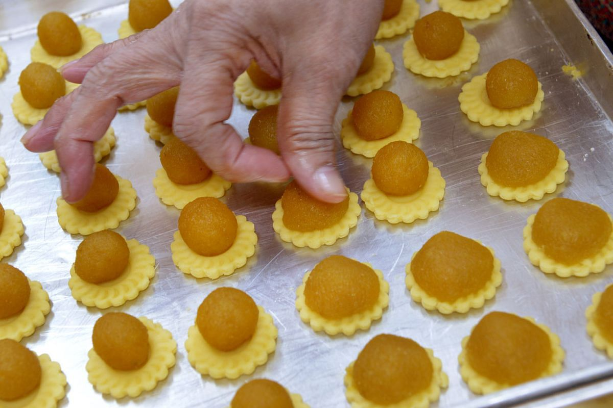 The balls of pineapple jam being pressed onto the pastry. Pine Garden's Cake uses the same ingredients it has used through the years.