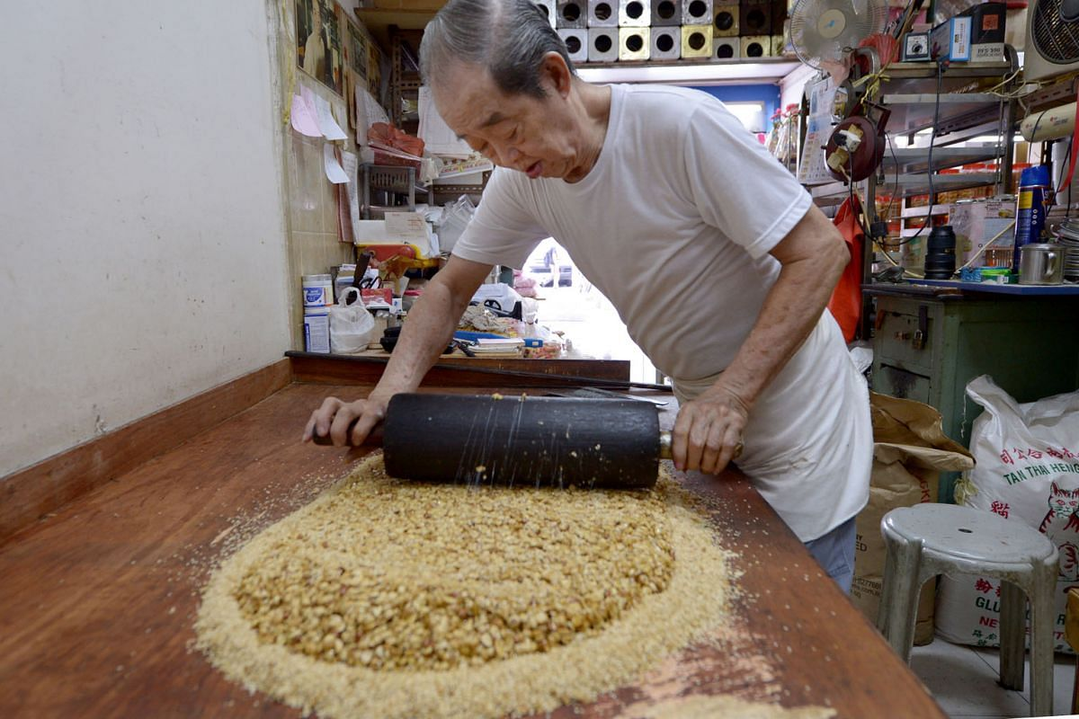 Mr Koh moulding the cooked sweetened peanut mixture into a large rectangular block to be cut into bite-size pieces. Today, his traditional peanut candy competes with the wide variety of snacks available.