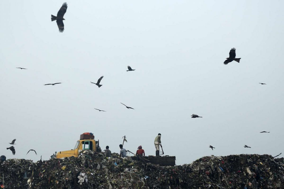 Workers unload waste from a truck at the second modern sanitary landfill at Aminbazar in Dhaka, Bangladesh on Feb 4, 2016.