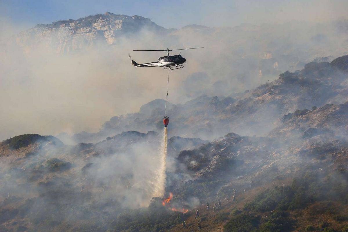 A fire fighting helicopter flies through thick smoke as it battles a blaze on the slopes  in Cape Town, South Africa on Feb 4, 2016.
