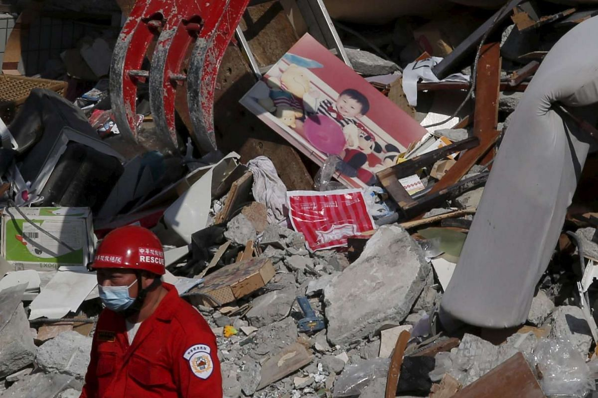A photo of a child is seen among the ruins of a 17-storey apartment building that collapsed after an earthquake hit Tainan, southern Taiwan on Feb 7, 2016.