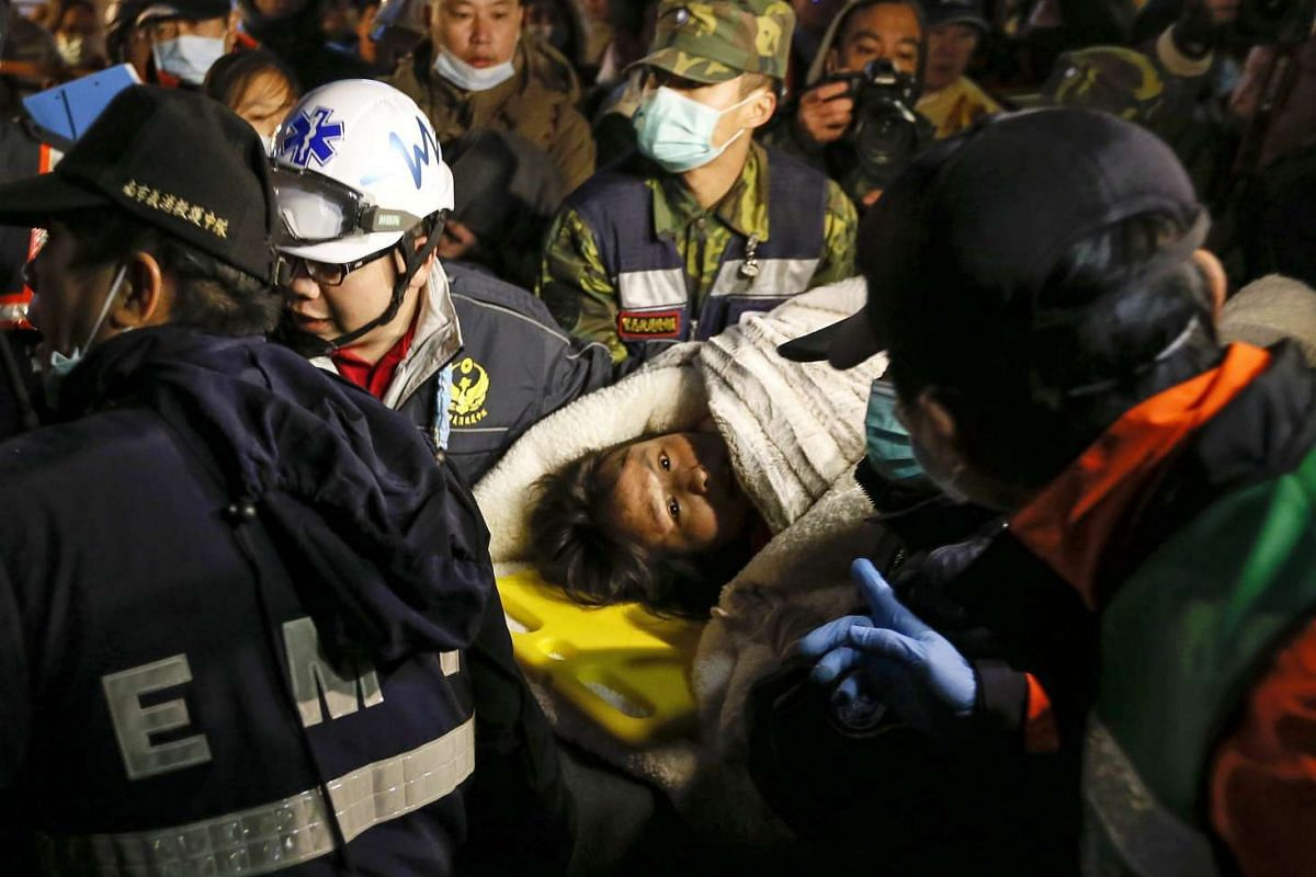 Rescuers carry a survivor from a collapsed building following an earthquake in Tainan City, Taiwan, on Feb 6, 2016.