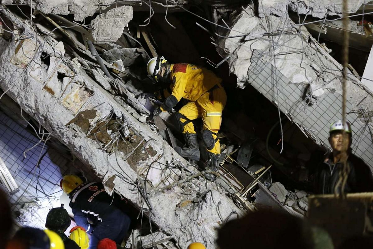 Rescuers remove obstacles as they continue to search for survivors trapped in a building following an earthquake in Taiwan, on Feb 6, 2016.
