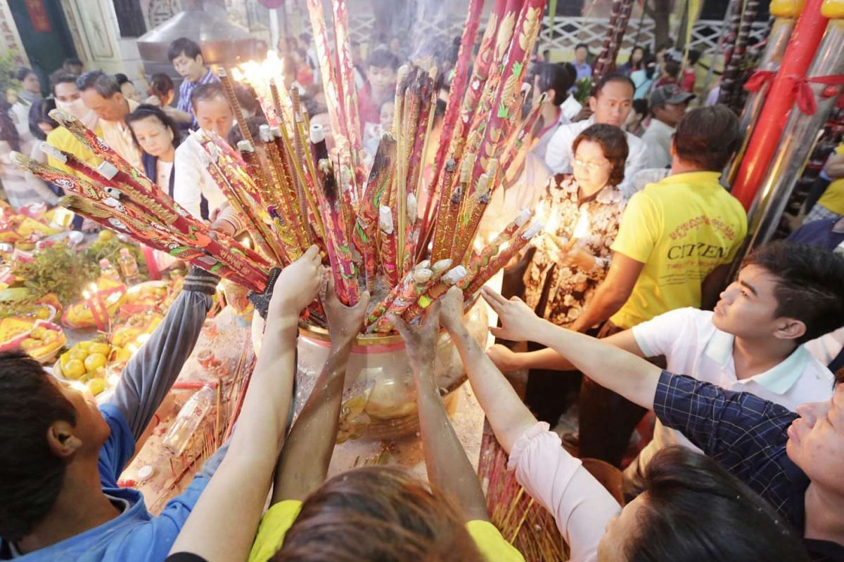 Cambodians burn incense to pray at a Chinese temple during the Chinese New Year celebration in Kandal province, Cambodia, on Monday (Feb 8).