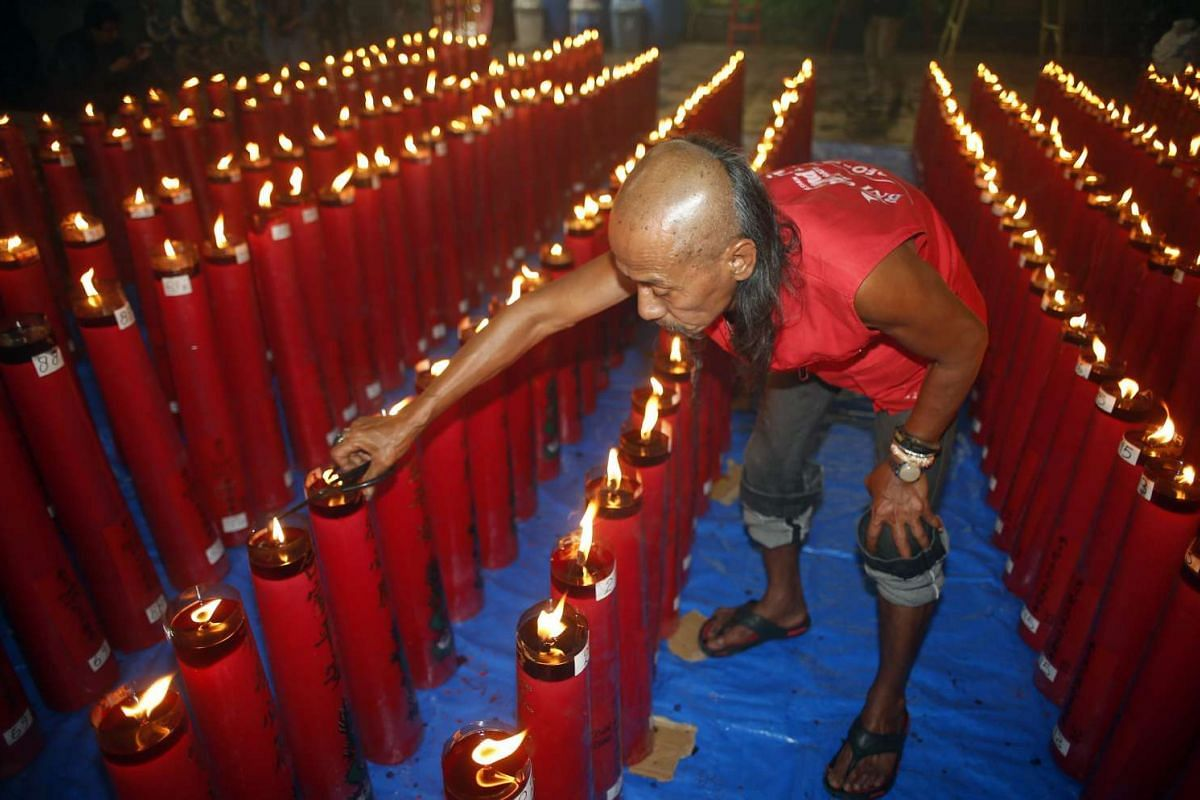 A worker holds a scissors as he organises candles during the Chinese New Year celebrations at a temple in Bogor, Indonesia, on Monday (Feb 8).