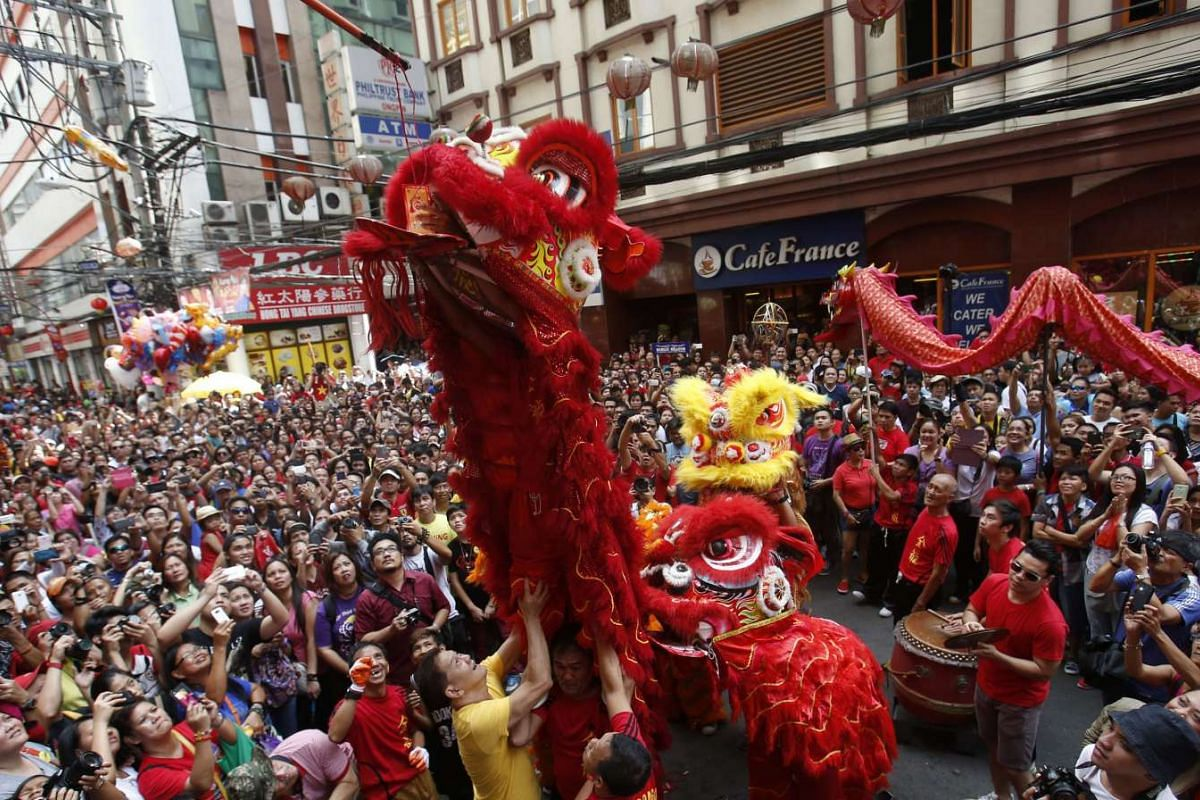 A lion dancer receives a red envelope or hongbao containing money during a celebration of the Chinese New Year in Manila's Chinatown, Philippines, on Monday (Feb 8).