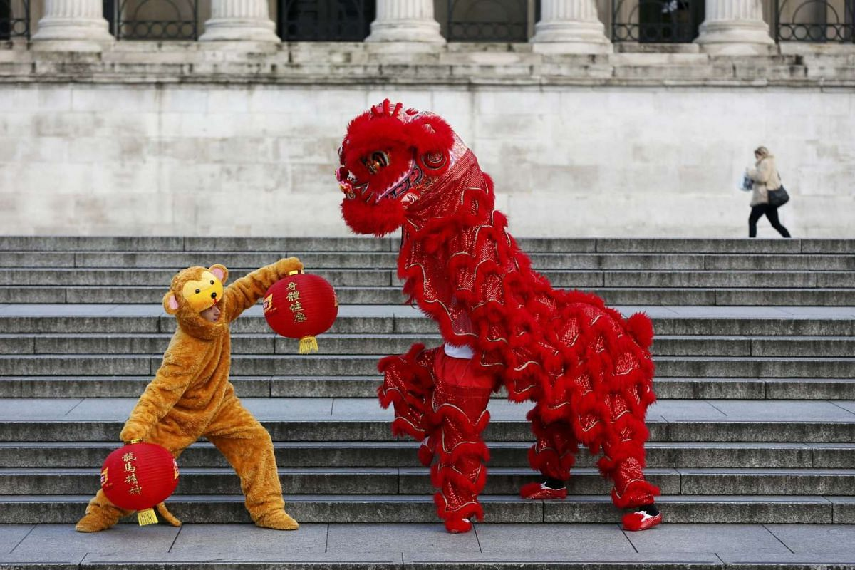 Performers in a lion and a monkey costume pose during a photo call to welcome in the Chinese New Year of the Monkey in Trafalgar Square, Britain, on Monday (Feb 8).