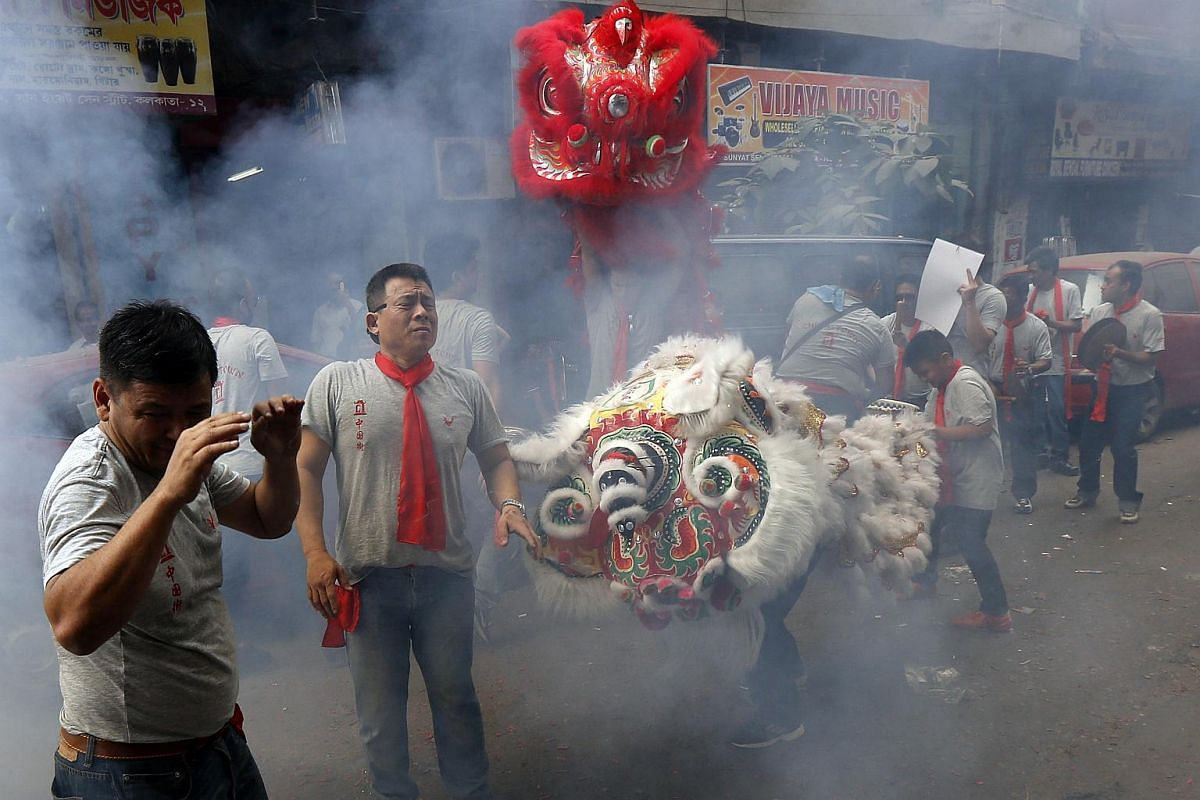 Men reacting as firecrackers explode while performing a lion dance during the celebrations to mark the Chinese New Year in Kolkata, India, on Feb 8, 2016.