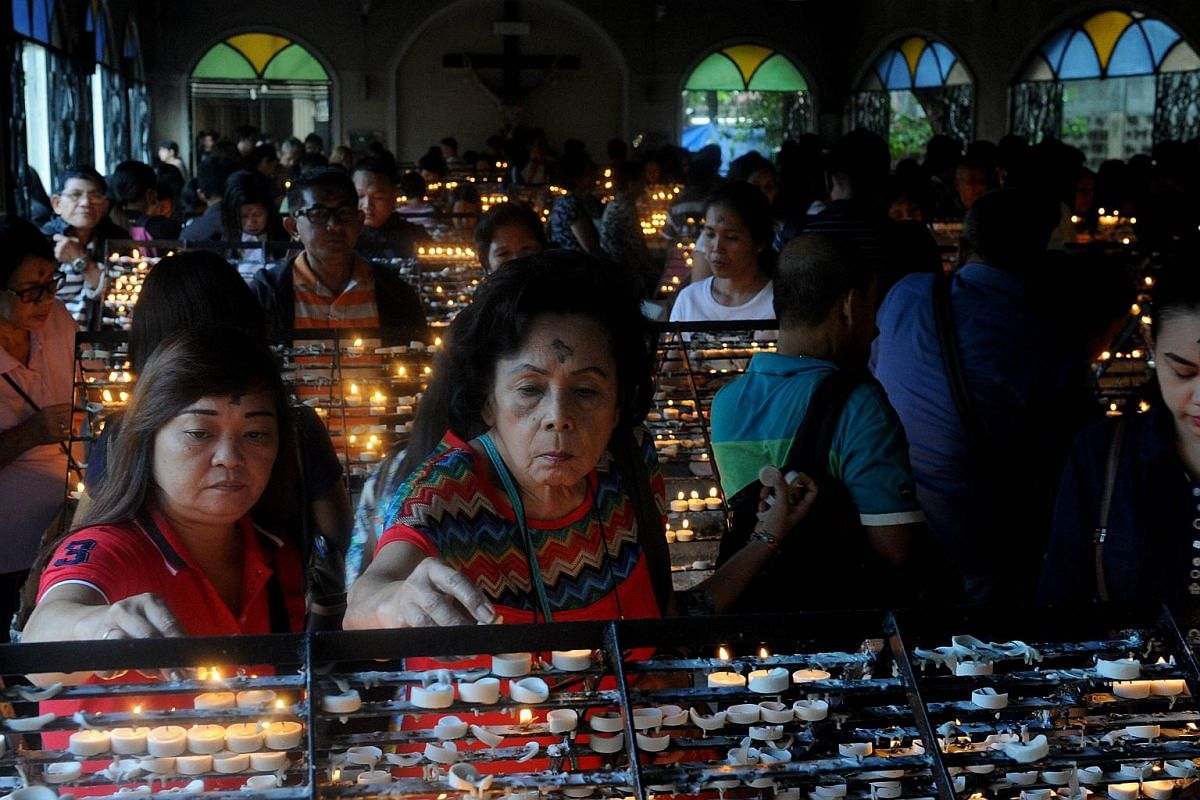 Roman Catholic devotees light candles at a church as the country marks Ash Wednesday, the official beginning of the Christian Lenten season in Manila on Feb 10, 2016.