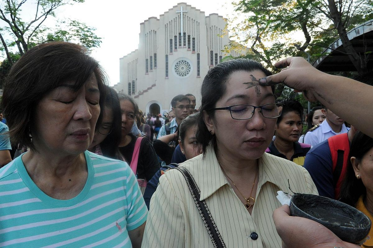 Filipino Catholics queue up to have crosses etched to their foreheads with ash as the country marks Ash Wednesday in Manila on Feb 10, 2016.