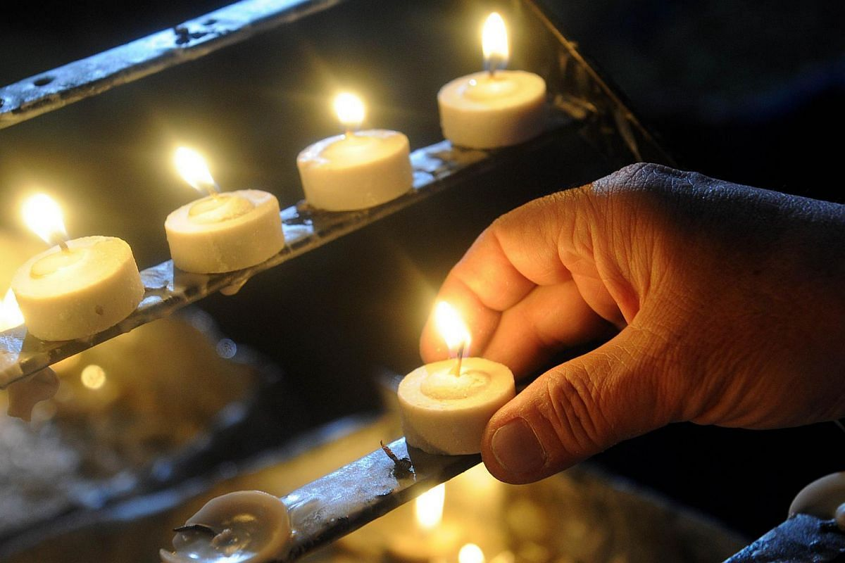 Roman Catholic devotees light candles at a church as the country marks Ash Wednesday in Manila on Feb 10, 2016.