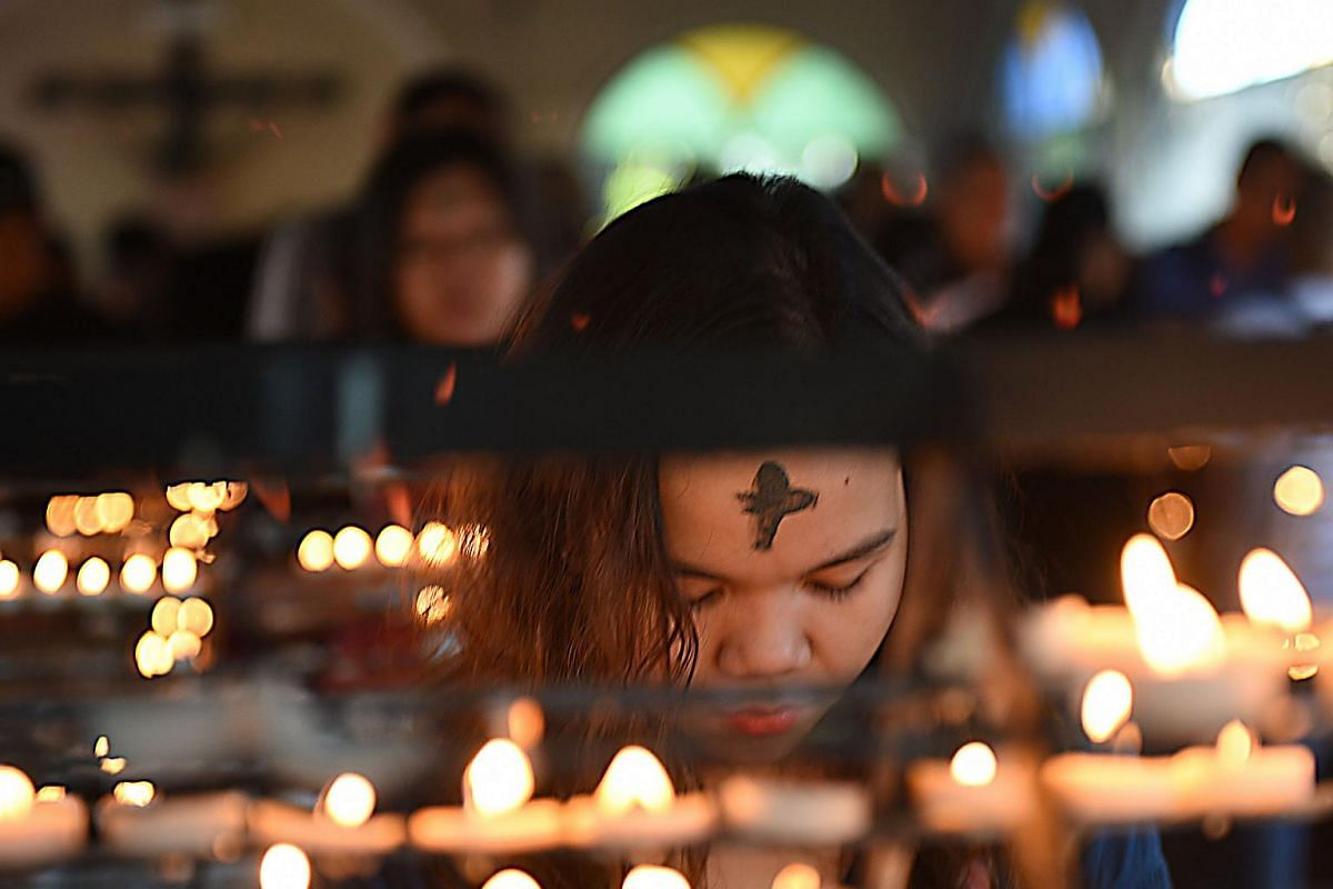 A woman prays next to lighted candles during the observance of Ash Wednesday which marks the start of Lent, at a church ground in Manila on Feb 10, 2016.