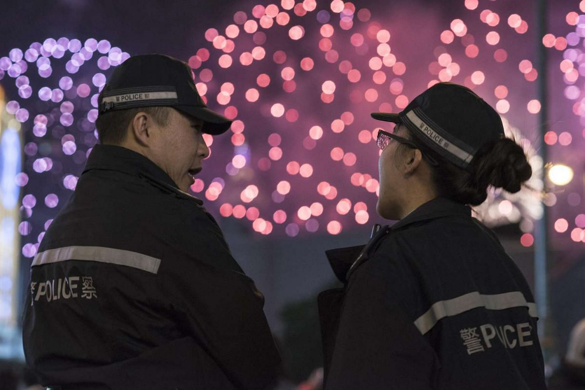 Police officers stand on the street as fireworks explode during the Chinese New Year celebrations. This following the previous night's rioting in Kowloon's Mong Kok district, in Hong Kong.