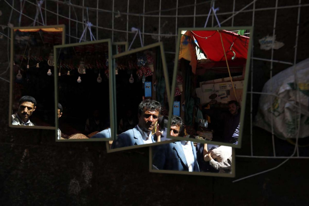 Yemenis are reflected in mirrors as they shop at a market in the old city of Sana'a, Yemen.
