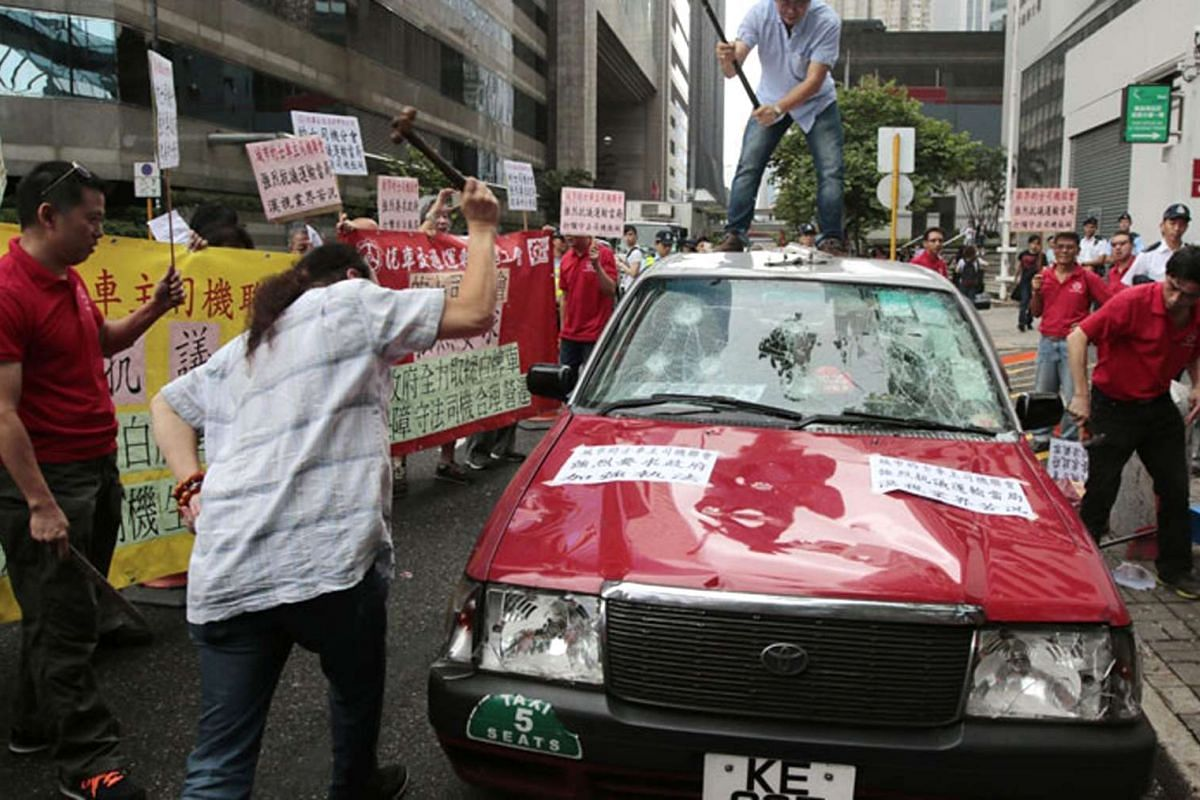 Cabbies in Hong Kong vent their anger towards Uber taxis by smashing a cab.