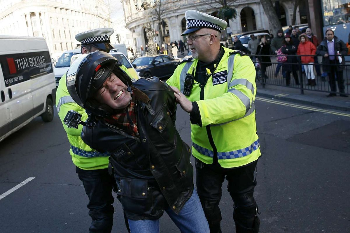 A man is detained by police officers during a protest by London cab drivers against Uber in central London.