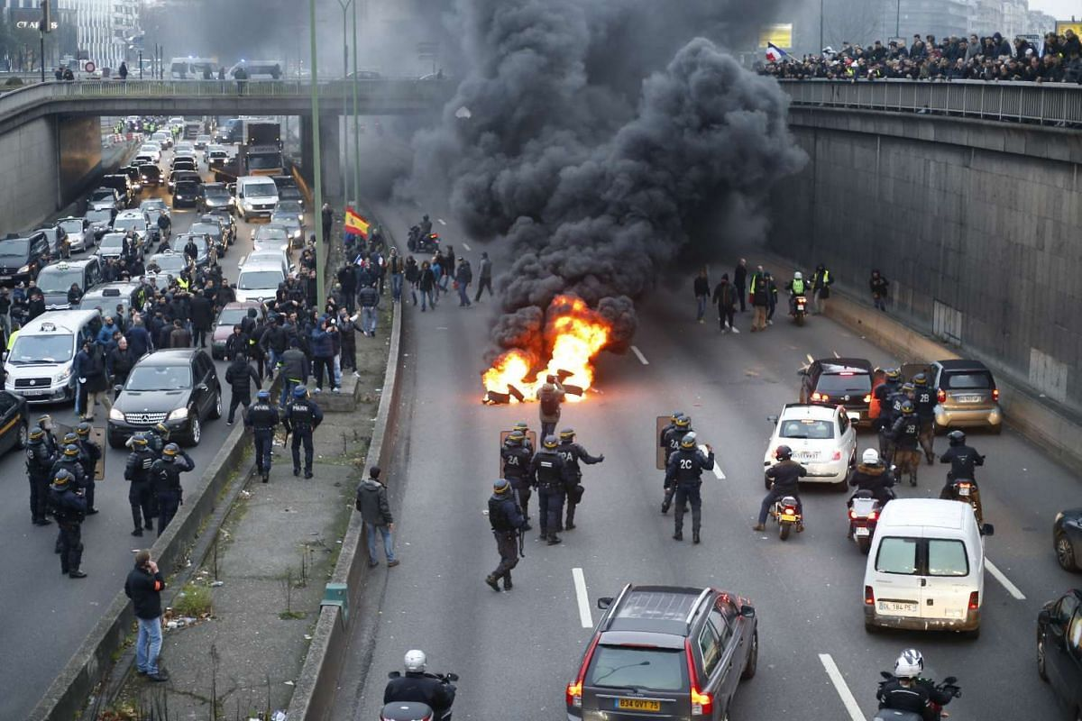 Anti-riot policemen arrive as taxi drivers block traffic during a demonstration at Porte Maillot in Paris.