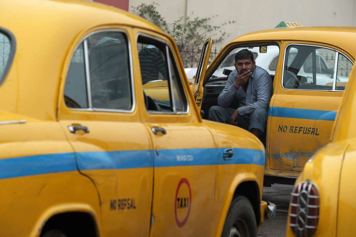 An Indian taxi driver sits in his vehicle as he waits for passengers in Kolkata.