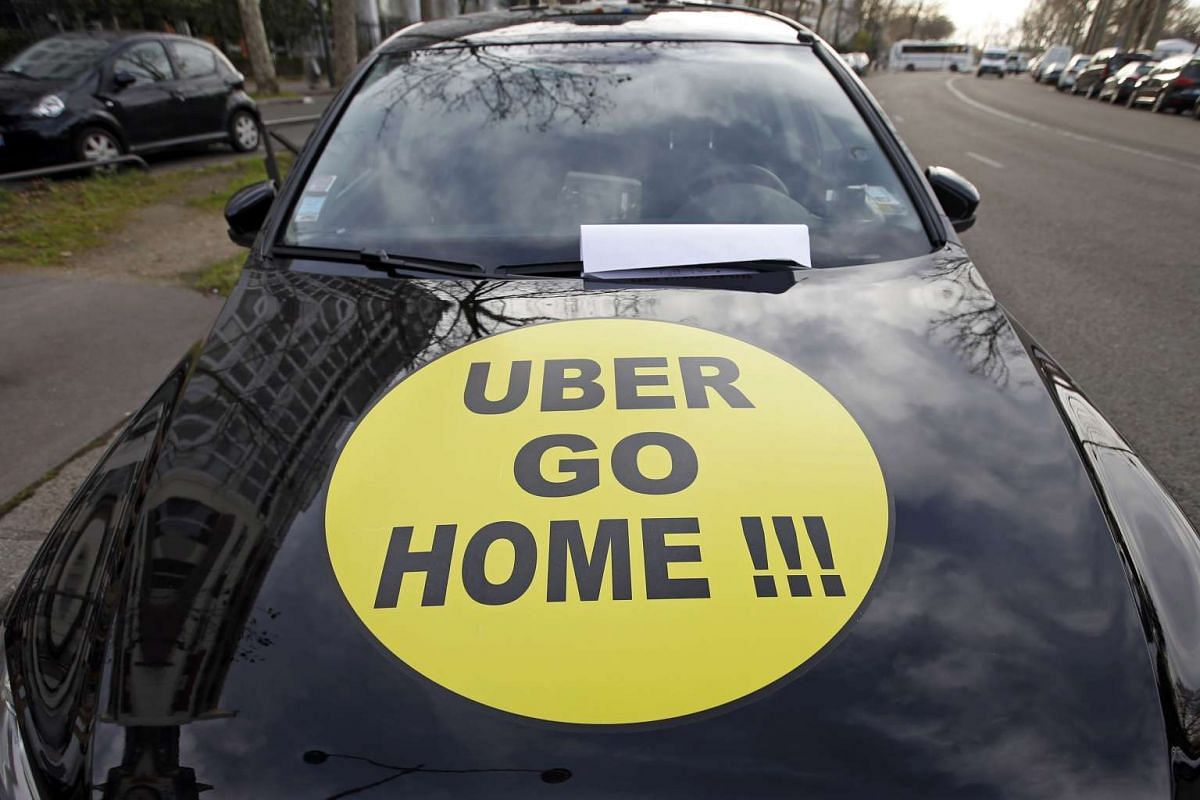 """A striking French taxi driver displays the message, """"Uber Go Home"""" during a national protest against Uber in Paris, France."""