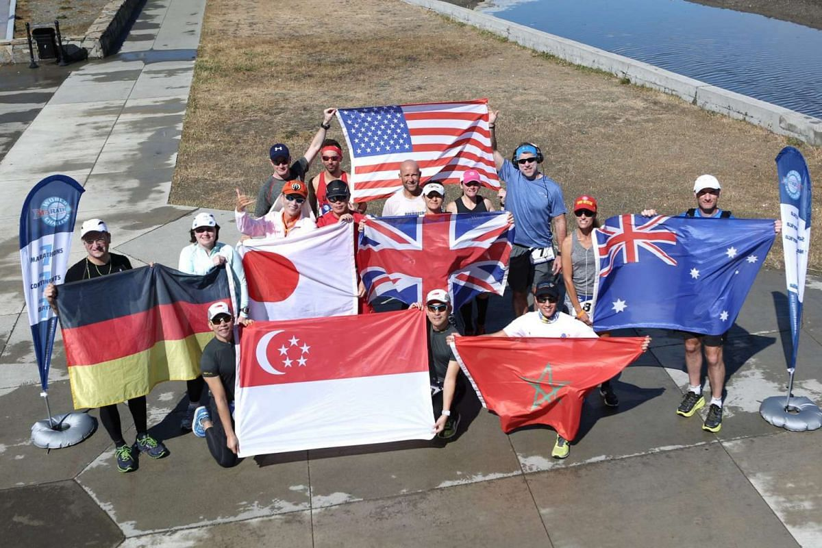 Cousins Ong Yu-Phing (left) and Ong Tze Boon holding the Singapore flag with other participants of the 2016 World Marathon Challenge in Punta Arenas, Chile, last month. They ran a total of 295km across seven continents, and had to cope with different