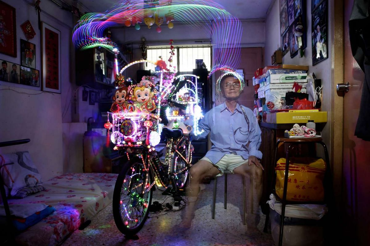 Mr Cheong at home with his decorated electric bicycle. He conceptualises the designs and puts up the LED lights and decorations himself. For Chinese New Year, he changed the design at the back of the bike from a Christmas tree to peach blossoms. He l