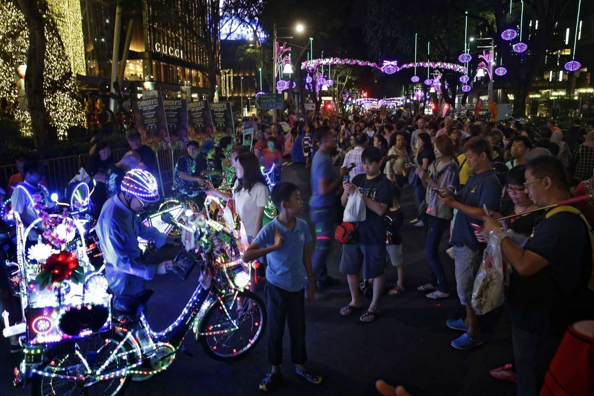 Mr Cheong (above, front left), and Mr Peter (behind Mr Cheong) parading their electric bicycles alongside other performers from People's Association to promote Chingay during Pedestrian Night in Orchard Road on Jan 2; Mr Cheong with his brightly li