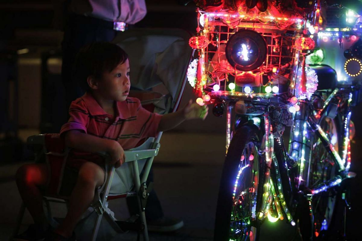 A child reaches out to touch an ornament on Mr Cheong's electric bicycle. Mr Cheong keeps a keen eye out for intrusive hands that might damage his decorations.