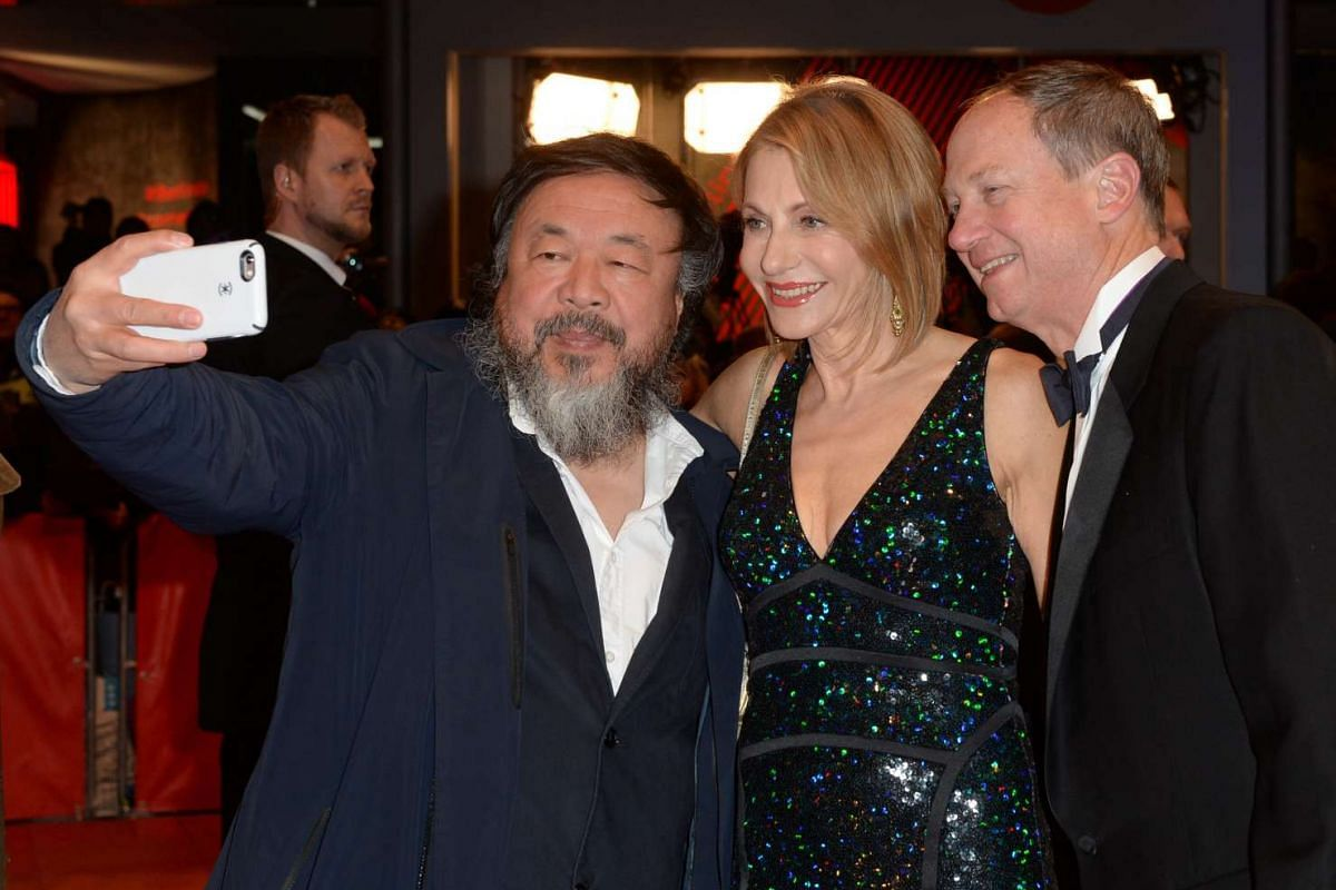 Chinese artist Ai Weiwei takes a selfie with US ambassador to Germany, John B. Emerson (right) and his wife Kimberly at the Opening Ceremony of the 66th annual Berlin International Film Festival on Feb 11, 2016.