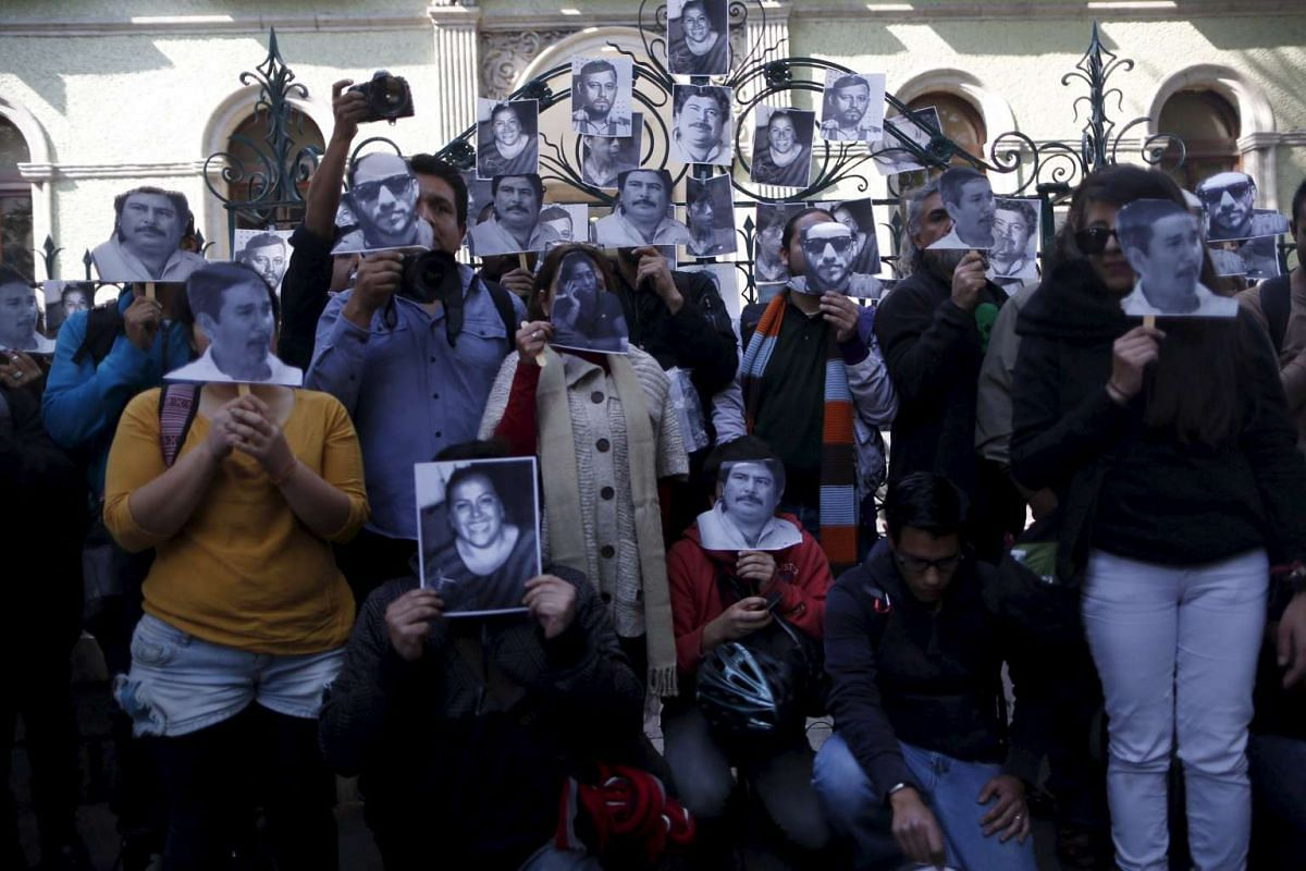 Journalists and activists holding images of murdered journalists during a demonstration against the murder of a journalist Anabel Flores outside the Government of Veracruz building in Mexico City on Feb 11, 2016.