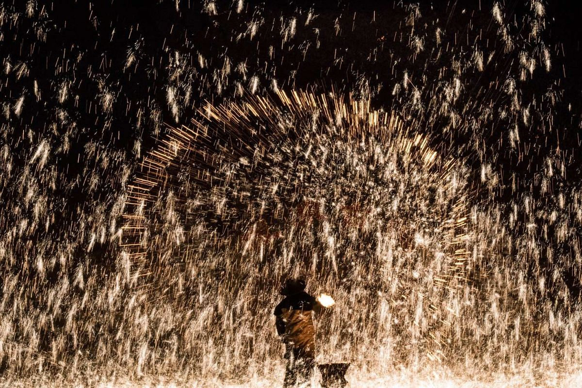 A Chinese blacksmith throwing molten metal against a cold stone wall to create sparks, during the Lunar New Year celebration in Nuanquan, Hebei province, China on Feb 11, 2016.
