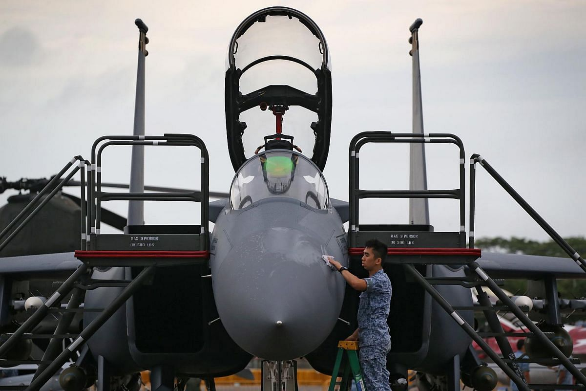 An RSAF personnel cleaning an F-15SG fighter aircraft at the Singapore Airshow 2016 static display area.