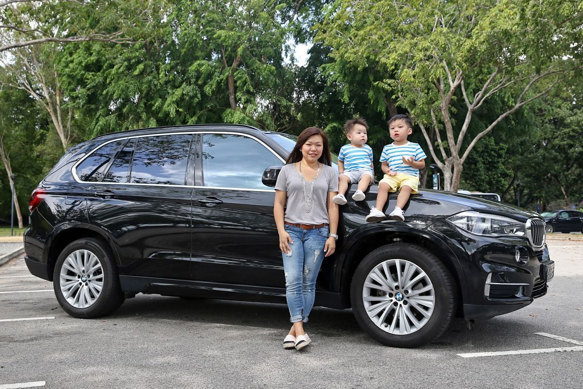 Ms Dawn Lim and her sons Harry and Ryan Ha with the family's BMW X5, which she finds a bit thirsty.