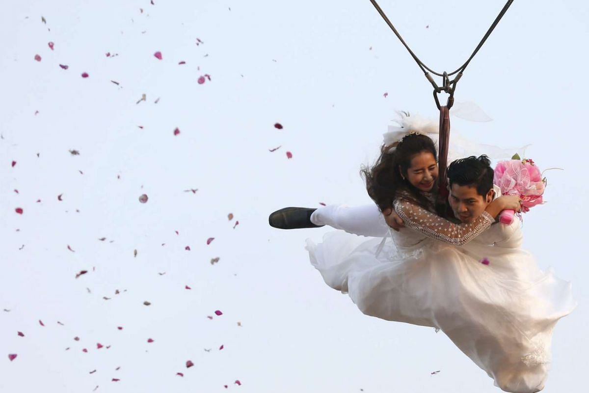 Kittinant Suwansiri holds his bride Jintara Promachat on a zip-line during their aerial wedding ceremony as part of the Thailand Adventure Wedding 2016 to celebrate Valentine's Day in Thailand on Feb 13, 2016.