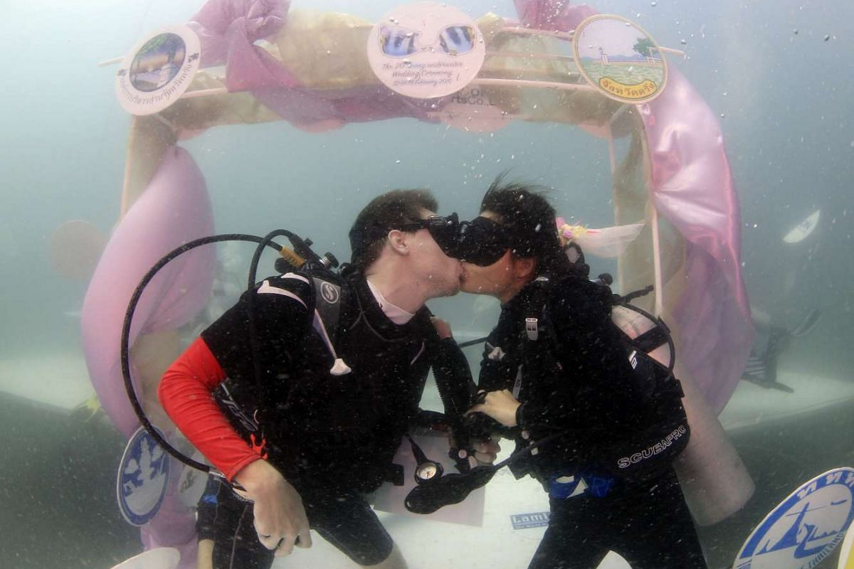 Swedish groom Niclass Zerne (left) kissing his Thai bride Pichaya Ploychaereon during an underwater wedding ceremony in the Andaman Sea, Thailand, on Feb 13, 2016.