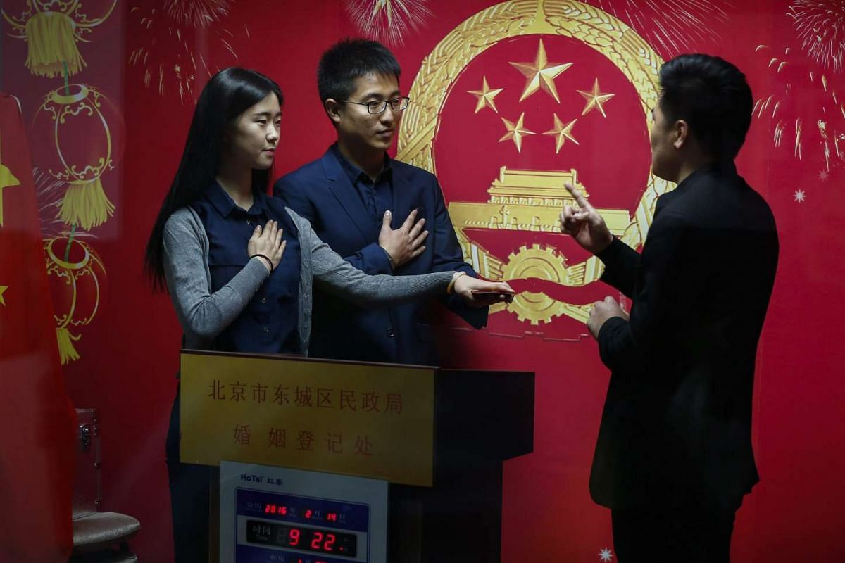 A marriage registry office facilitator conducts a symbolic ceremony to hand over marriage licences to a Chinese couple on Valentine's Day in Beijing, China.