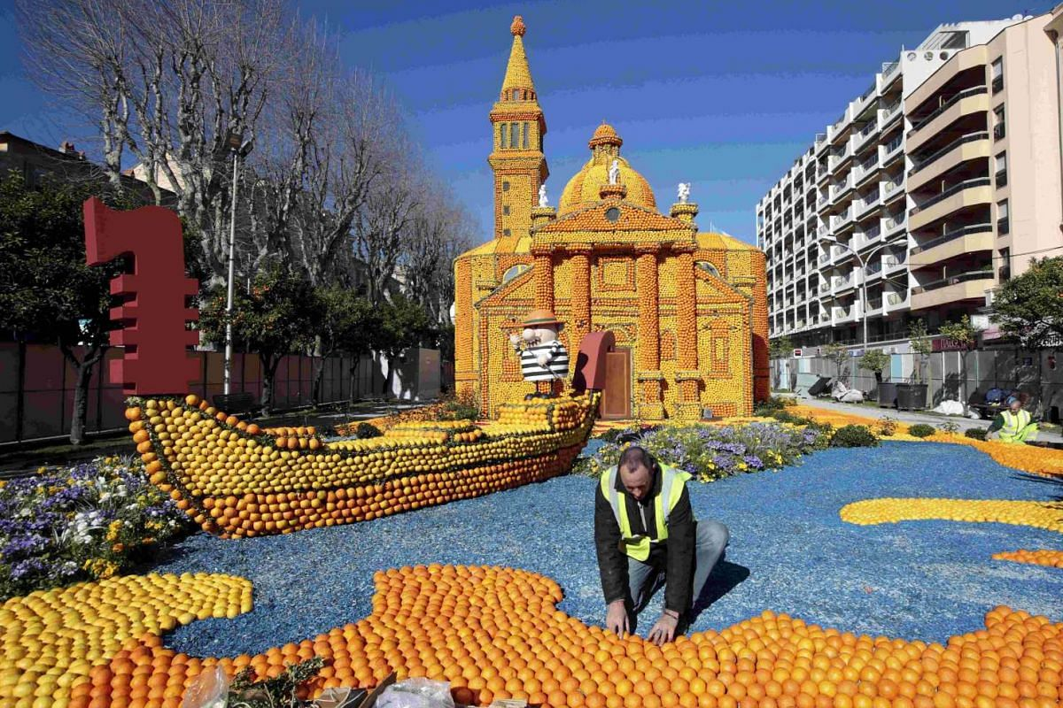 A worker puts the final touch to a gondola and a Venetian palace replica at the Lemon festival in Menton, France on Feb 10, 2016.
