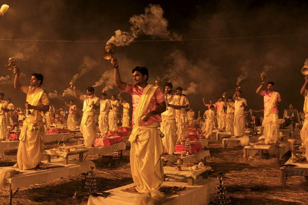 """Hindu priests hold traditional incense lamps as they perform a ritual known as """"Aarti"""" on the banks of Sangam during the annual religious festival of Magh Mela in Allahabad, India on Feb 14, 2016."""
