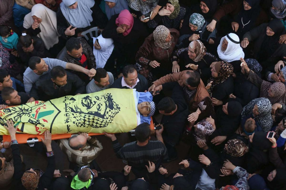 Mourners carry the body of Palestinian teenager Nihad Waked, 15, who was shot dead by Israeli troops on Sunday, during his funeral near the West Bank city of Jenin on Feb 14, 2016.