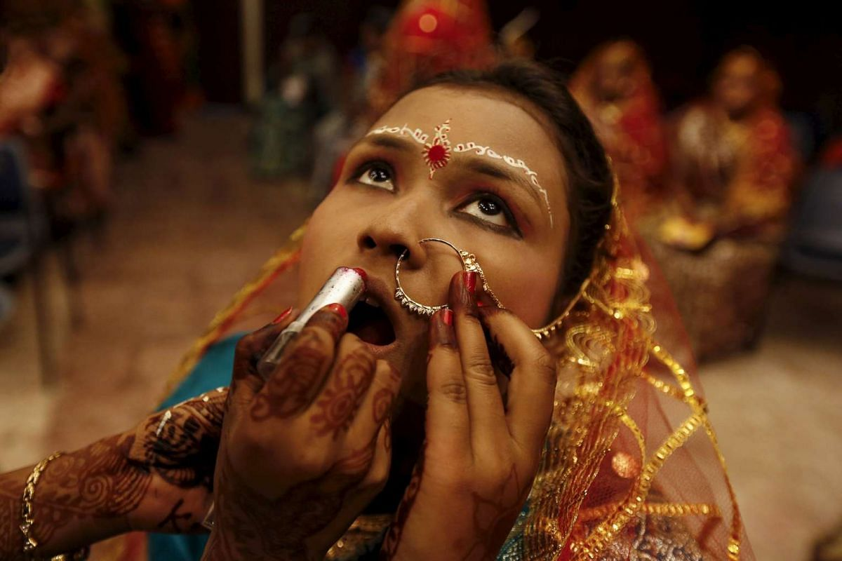 A bride gets her make-up done before the start of a mass marriage ceremony in Kolkata, India on Feb 14, 2016.