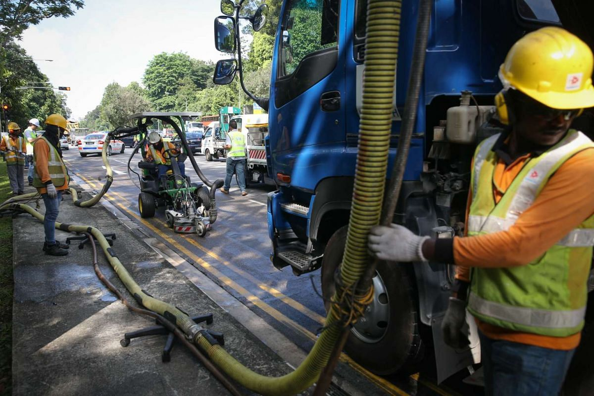 Workers cleaning up an oil spill along Lornie Road towards Adam Road on Feb 16, 2016. The oil spill, which was caused by a broken-down vehicle, led to a massive traffic jam this morning during peak hour. ST PHOTO: ONG WEE JIN