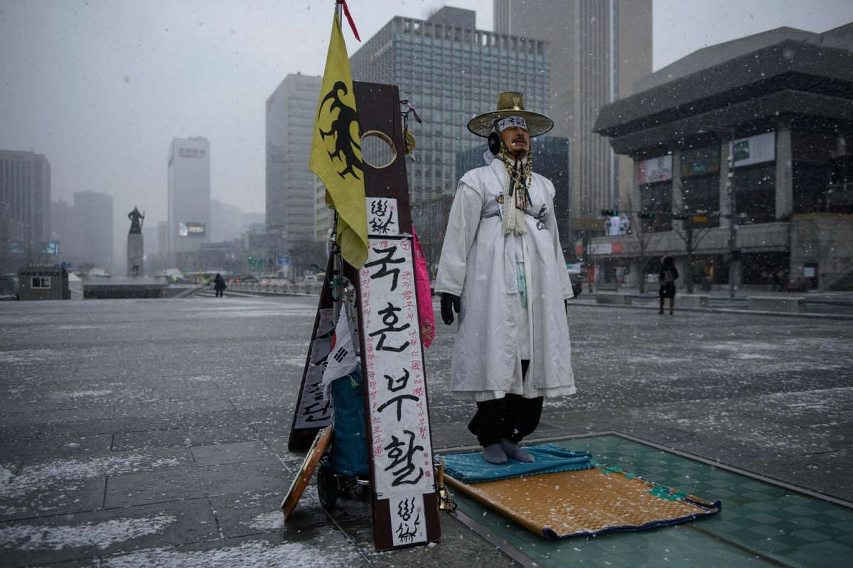 A man wearing a traditional Korean dress holds a protest calling for a return to traditional Confucian values, in central Seoul on Feb 16, 2016. PHOTO: AFP/ED JONES