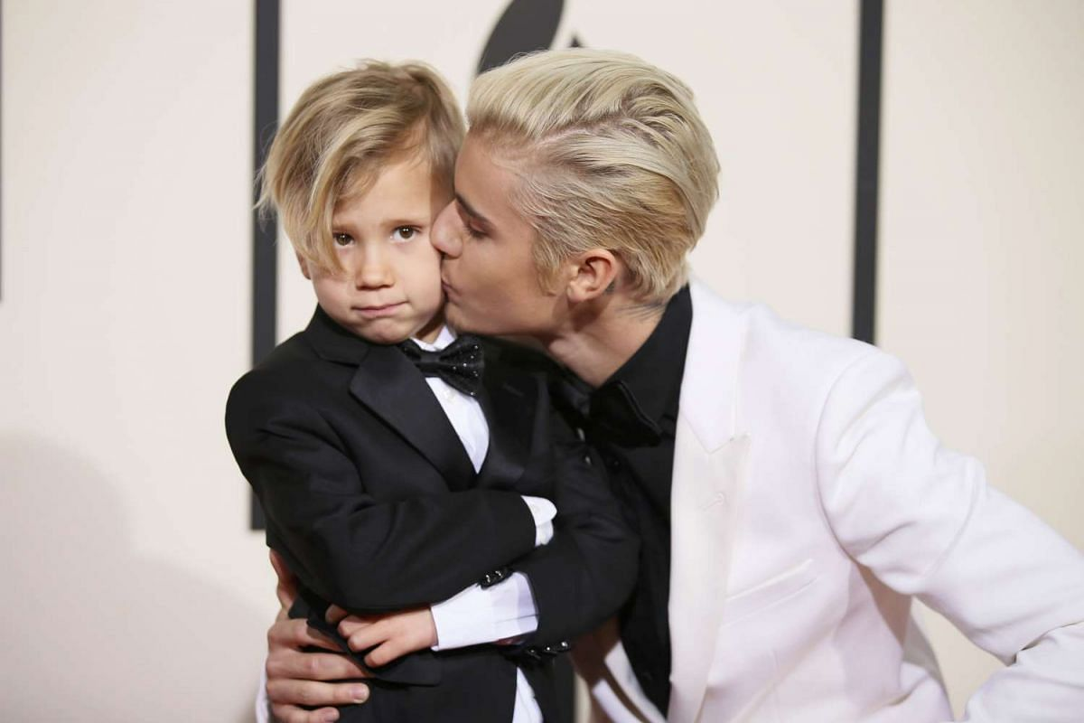 Justin Bieber (right) giving his brother Jaxson a kiss at the 58th Grammy Awards.
