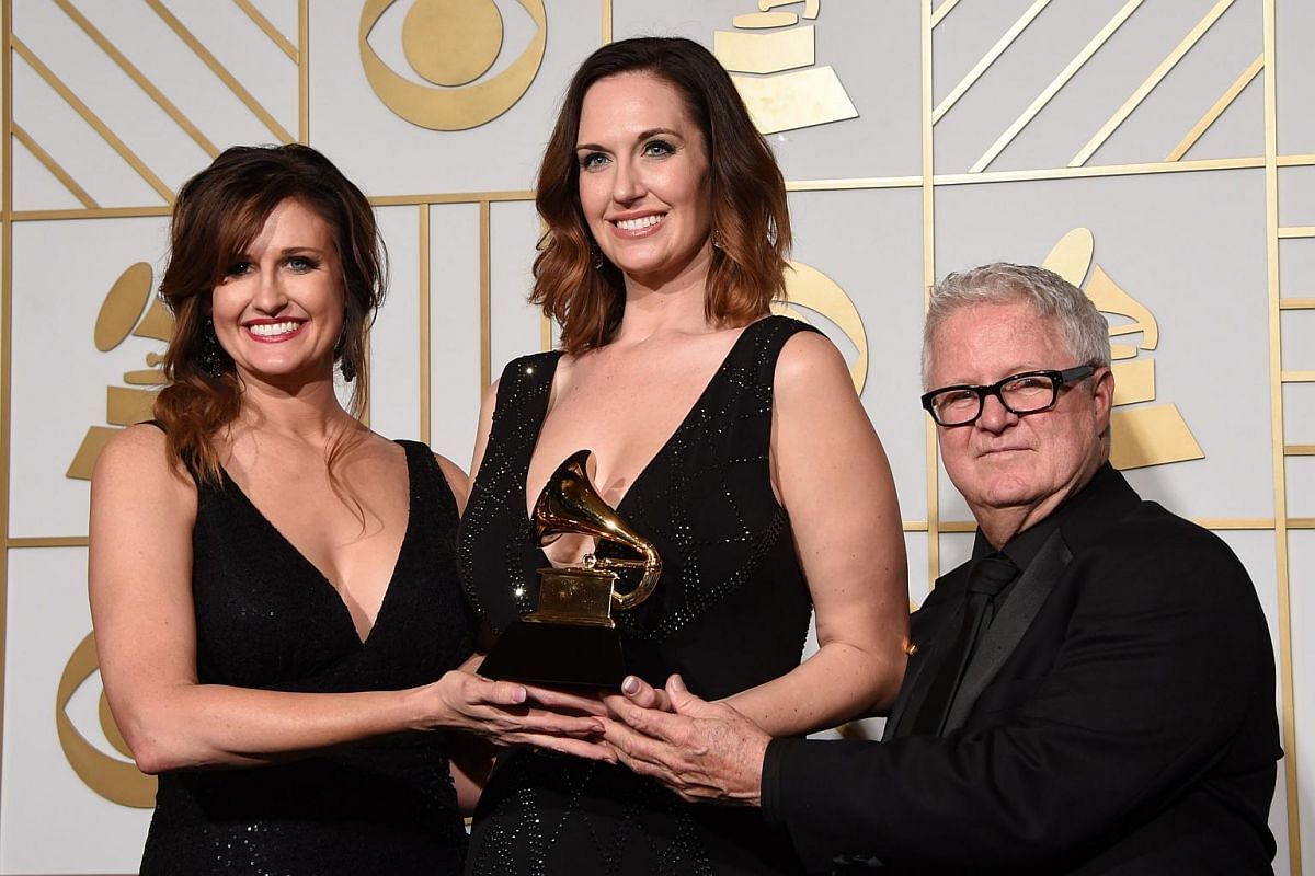 Art directors Saran Dodds, Shauna Dodds and Dick Reeves posing with the trophy for Best Recording Package Still The King in the press room during the 58th Annual Grammy Music Awards.
