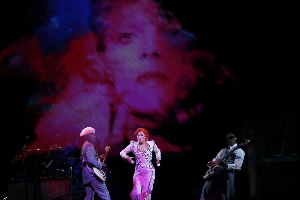 Lady Gaga performing a medley of songs as a tribute to the late David Bowie with Bowie collaborator guitarist Nile Rogers (left) at the 58th Grammy Awards.