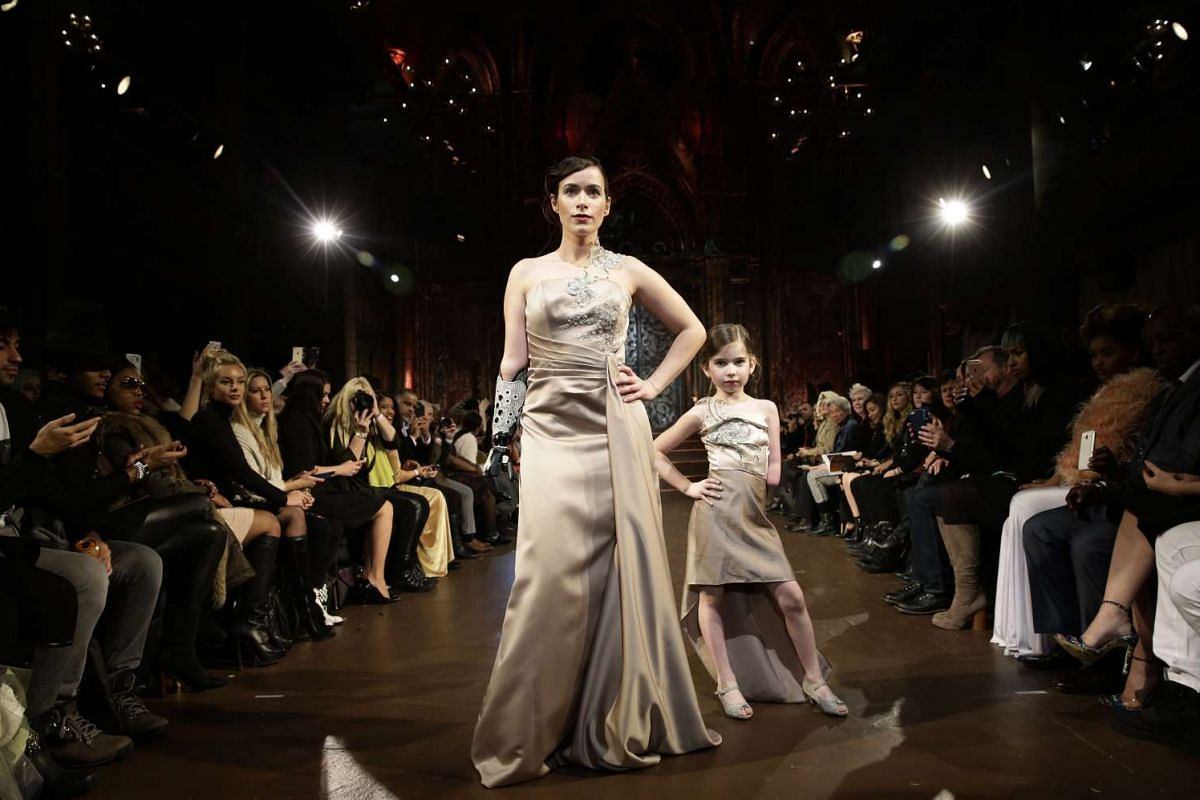 Bionic arm amputee model Rebekah Marine (left) and six-year old amputee model Gianna Schiavone (right) presenting creations from the Fall 2016 collection by FTL Moda during the New York Fall Fashion Week.
