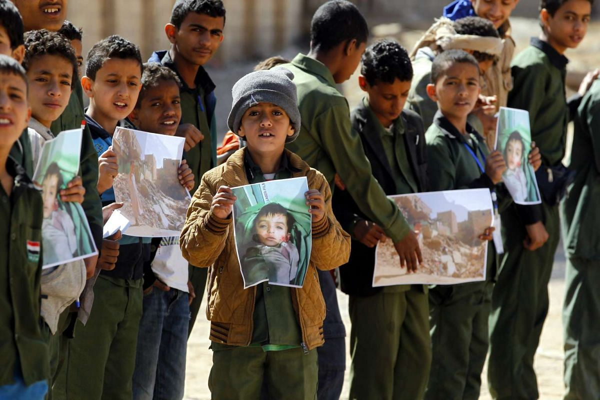 Yemeni pupils hold pictures of alleged air strike victims during a rally against the Saudi-led military operations in the war-torn country, at a school in Sana'a, Yemen, Feb 16, 2016. PHOTO: EPA/YAHYA ARHAB